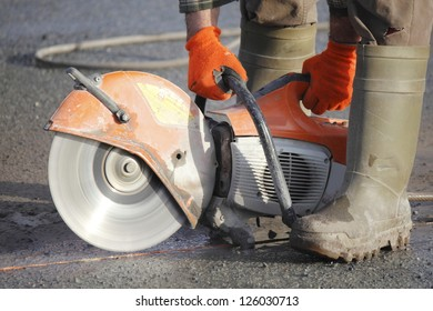 Profile on the blade of an asphalt or concrete cutter and workers boots/Profile on Asphalt Cutter/Profile on the blade of an asphalt or concrete cutter and worker's boots.