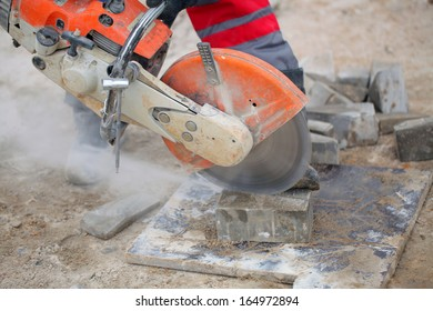 Profile on the blade of an asphalt or concrete cutter and workers boots .Construction worker using a concrete saw, cutting stones in a cloud of concrete dust for creating a track.