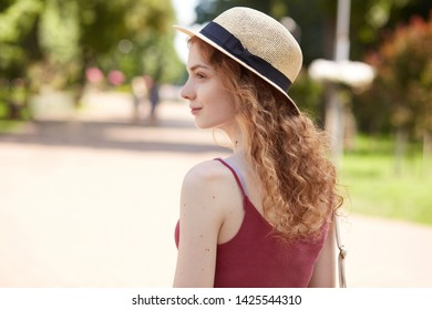Profile of pensive beautiful active girl wearing straw summer hat and red shirt, having pleasant facial expression, looking straightforward, having curly fair hair, enjoying her weekends in park.
