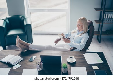 Profile photo of attractive self-confident business lady notebook table read corporate report writing details personal planner legs on table sitting chair modern interior office indoors