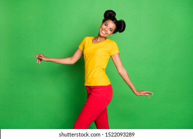 Profile photo of beautiful dark skin lady walking down street amazing sunny day weather wear casual yellow t-shirt and red pants isolated green background