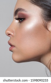 Profile photo of a beautiful girl with professional makeup, ideal skin, rose eyeshadows and nude lips.