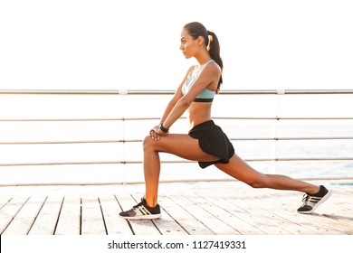 Profile photo of energetic brunette sportswoman 20s in tracksuit doing lunges and stretching legs on boardwalk at seaside