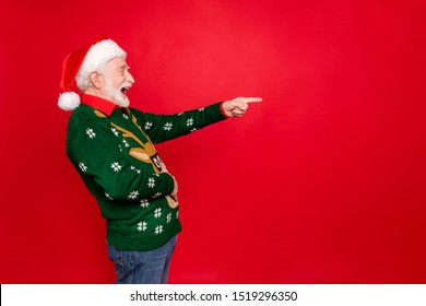 Profile photo of santa man indicating finger to empty space laughing of loser people holding hand on belly wear x-mas ugly ornament sweater cap isolated red background