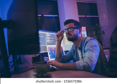 Profile photo of it specialist looking monitors testing website debugging system attentive developer expert creating new tasks for team sitting night office indoors