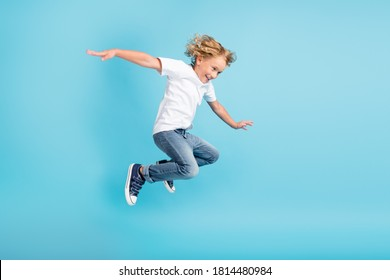 Profile photo of young boy jump fly movement hands wear white shirt jeans sneakers isolated blue color background