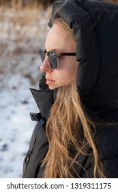 A profile photo of a young woman in a black jacket wearing sun glasses.