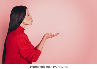 Profile photo of young woman holding her hands sending air kisses eyes closed over pink background