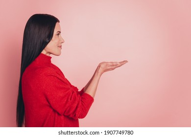 Profile photo of young woman holding her hands showing something on the open palms over pink background