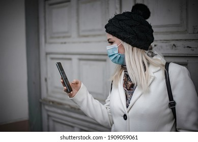Profile photo of young woman looking into her phone and wearing a face mask due to pandemic
