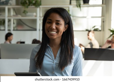 Profile picture of smiling African American millennial female employee posing in coworking space holding tablet, headshot portrait of happy biracial woman worker stand in office, internship concept