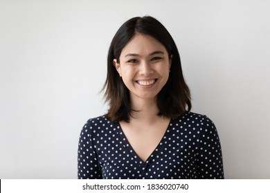 Profile picture of smiling millennial asian girl isolated on grey wall background look at camera posing. Headshot portrait of happy young Vietnamese woman renter or tenant satisfied with service.