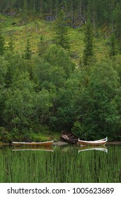 Profile picture of two wooden boats with white stripes close to each other, reflecting in the water near Mosjøen in Norway