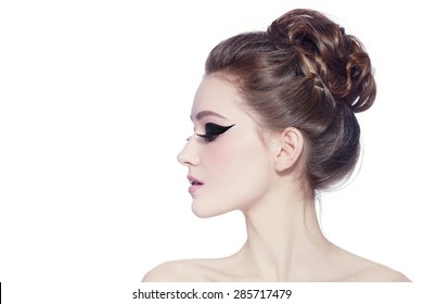 Profile poartrait of young slim beautiful girl with hair bun and fancy cat eyes over white background