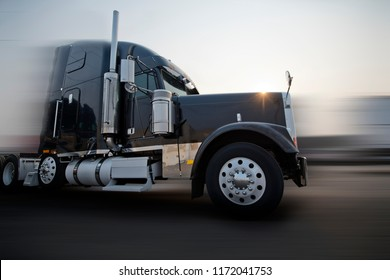 Profile of popular American dark bonnet classic big rig semi truck tractor with chrome and stainless steel accessories going on the road with sunshine in blurred background