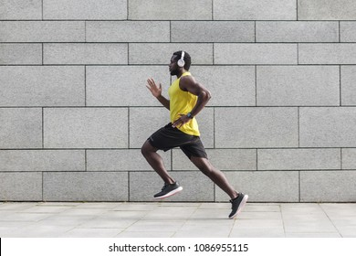 Profile portrait of adult male runner with muscular body in tracksuit jogging against gray wall with copy space area for text message or content