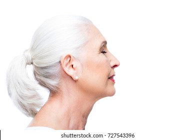 profile portrait of attractive senior woman with closed eyes, isolated on white