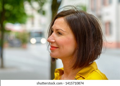 Profile portrait of an attractive stylish middle-aged woman standing in a street in town looking to the left of the frame with a smile
