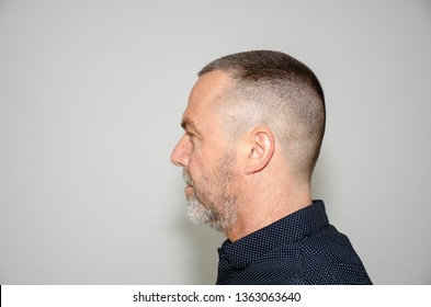 Profile portrait of a bearded middle aged man in stylish dark shirt with short modern haircut looking to the left side