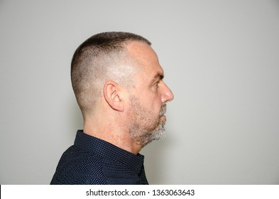 Profile portrait of a bearded middle aged man in stylish dark shirt with short modern haircut looking to the right side