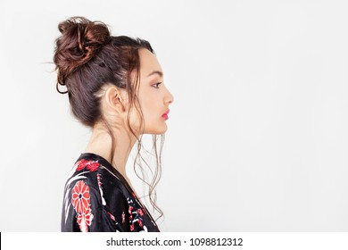 Profile portrait of beautiful asian ethnic young woman with hairdo up, wearing exotic robe against plain white background space, indoors. Healthy beauty portrait flawless skin, cosmetics lifestyle.
