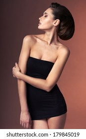 Profile portrait of a beautiful fashion woman in black dress with hairstyle - side view