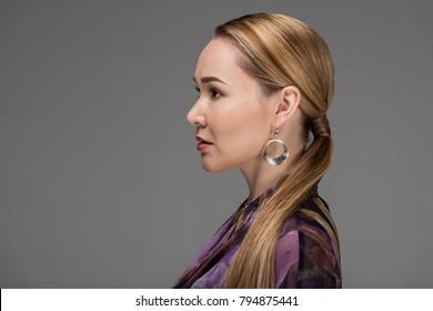 profile portrait of beautiful kazakh woman looking away isolated on grey