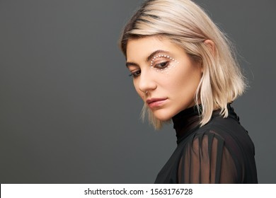 Profile portrait of beautiful stylish young blonde female in black transparent dress posing isolated looking down with sad facial expression, feeling upset. Shy unhappy cute girl looking down