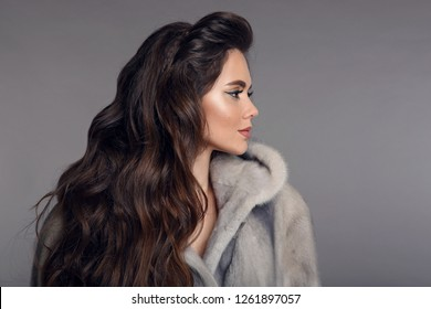 profile portrait of Beautiful woman with hood in mink fur coat isolated on gray studio background. Fashion Brunette Girl in Luxury Winter outerwear.