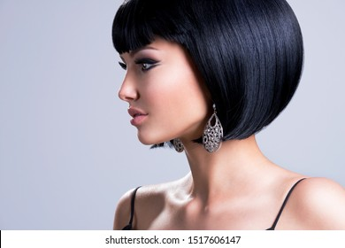 Profile portrait of a beautiful woman with shot hairstyle and fashion earring posing at studio