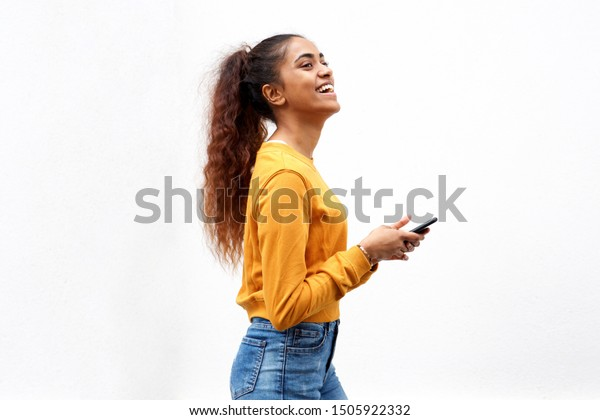 Profile portrait of beautiful young indian woman laughing at mobile phone by white background