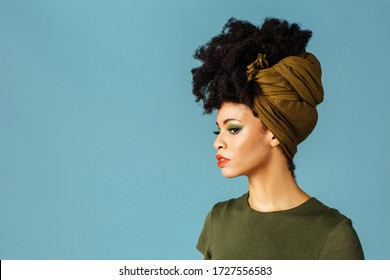 Profile portrait of a beautiful young woman in green head wrap scarf