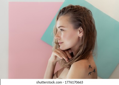 Profile Portrait of a Beautiful Young Woman with Birds Tattoo on the Shoulders. Gentle Pastel Colors Background. Authentic Beauty of Young Woman.