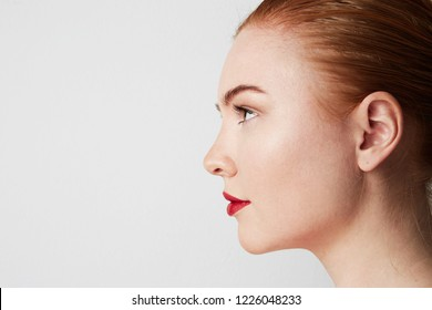 Profile portrait of beauty female redhead model with dark eyebrows and light nude make-up. Copy paste place
