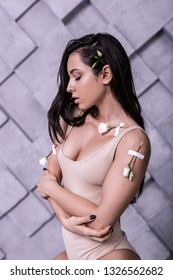 Profile portrait of bewitching seductive supermodel with shiny long dark hair crossing arms in studio photo session