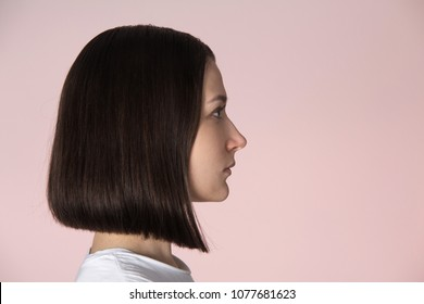 Profile portrait of brunette girl with bob hairstyle isolated on pink background. Hairstyles and hairdresser salon theme. Studio shot. Close-up view.