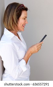 Profile portrait of businesswoman looking at mobile phone