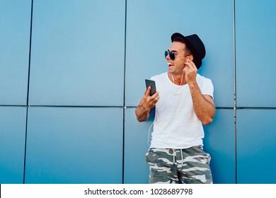 Profilporträt eines fröhlichen jungen Mannes in einer Sonnenbrille, der Musik im Headset auf dem Handy hört. In modischen Kleidern verkleidet. Draußen. Leerzeichen kopieren