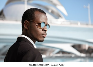 Profile portrait of confident good-looking young dark-skinned manager wearing fashionable sunglasses and black suit standing outdoors with modern office building in background on his way to work