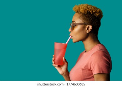 Profile portrait of a cool young  woman in pink holding a drinking cup and paper straw