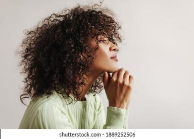 Profilporträt von geschmeidig brunette Frau in grüner Spitze aussehen einfach. Dunkelhäutige Dame auf weißem Hintergrund.