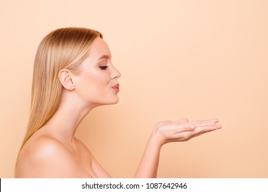 Profile portrait of cute, lovely, charming model blowing kiss with pout lips holding copyspace empty place on two palms looking at product isolated on beige background, advertisement concept