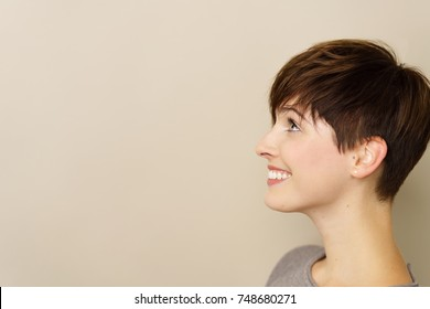Profile portrait of a cute modern young woman in a close up head shot as she looks towards blank copy space with a smile