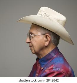 Profile portrait of elderly man wearing plaid shirt and cowboy hat.