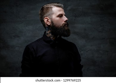 Profile portrait of an expressive bearded man with tattoos on his neck