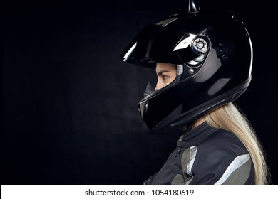 Profile portrait of fashionable young European woman rider with blonde hair preparing for motor race standing isolated wearing new black motorcycle safety helmet, having focused determined look