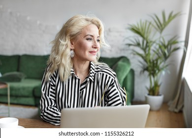 Profile portrait of gorgeous beautiful sixty year old female psychologist with blonde dyed hair and make up working on laptop computer, sitting at desk with mug, looking sideways and smiling