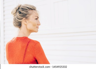 Profile portrait of a gorgeous blond woman with a beautiful face, straight nose and thick eyelashes, tanned skin with freckles. Minimalistic conceptual authentic woman portrait with copy space.