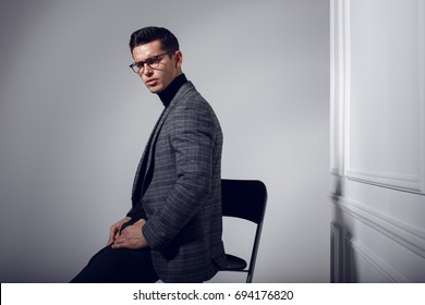 Profile portrait of a handsome, confident, elegantly man in black-gray suit and eyeglasses, posing in studio isolated on white background.  Horizontal view.