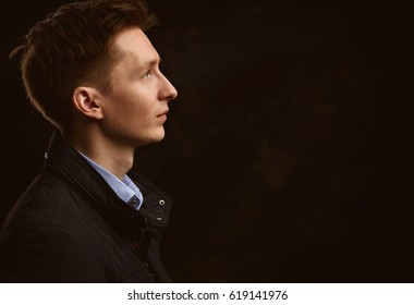 profile portrait of a handsome young man over black background